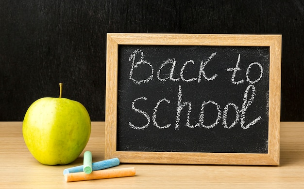 Frontowy widok blackboard z jabłkiem dla z powrotem szkoła