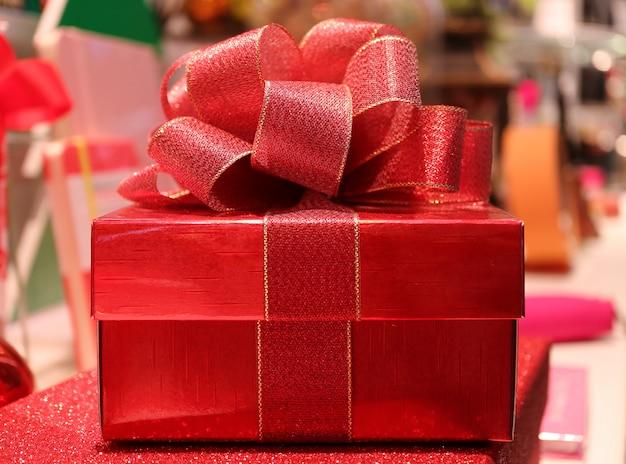 Frontowy widok błyszczący placu czerwonego prezenta pudełko z błyskotliwością czerwoną tasiemkową łękiem na zamazanym tle