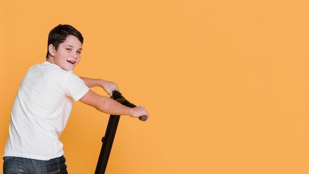 Frontowy widok chłopiec z hulajnoga z kopii przestrzenią