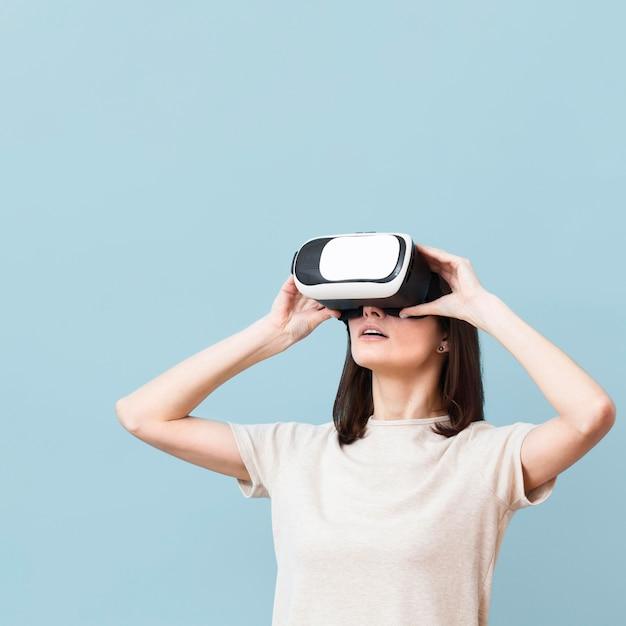 Frontowy widok cieszy się patrzeć przez rzeczywistości wirtualnej słuchawki kobieta
