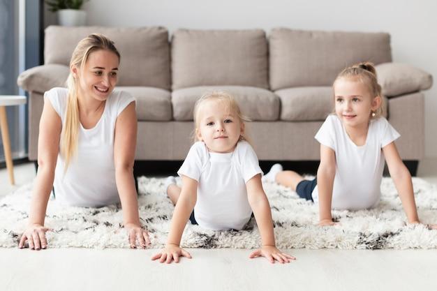 Frontowy widok ćwiczy w domu z córkami szczęśliwa matka