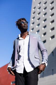 Frontowy widok czarnego afrykanina mężczyzna jest ubranym eleganckie ubrania stoi na ulicie podczas gdy patrzejący daleko od w słonecznym dniu