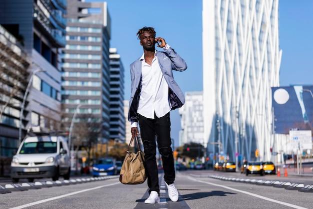 Frontowy widok czarnego afrykanina młodego człowieka odprowadzenie na ulicie jest ubranym elegancką kurtkę i trzyma torbę podczas gdy używać telefon w słonecznym dniu