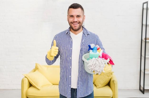 Frontowy widok daje aprobatom mężczyzna podczas gdy trzymający czyści produkty