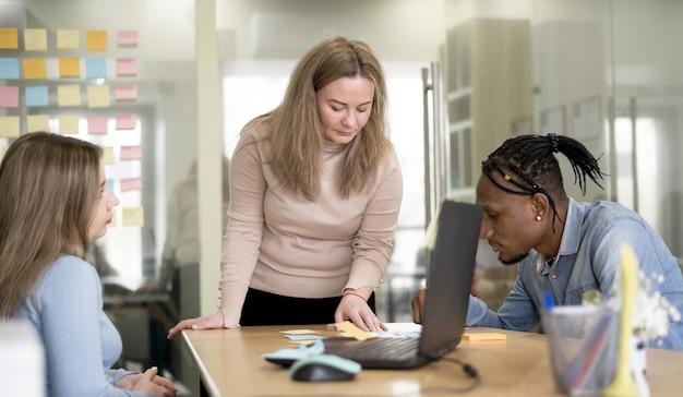 Frontowy widok daje prezentaci ludzie przy biurem kobieta