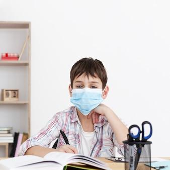 Frontowy widok dziecko z medyczną maską robi jego pracie domowej