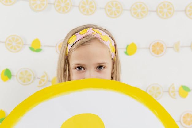 Frontowy widok dziewczyny mienia cytryny plasterka dekoracja