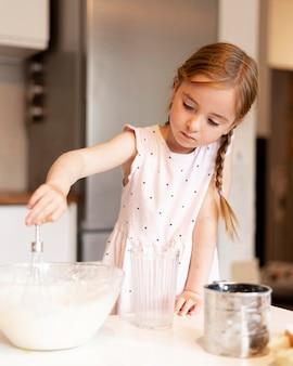 Frontowy widok gotuje w domu mała dziewczynka