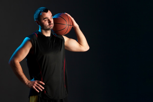 Frontowy widok gracz koszykówki z piłką na ramienia i kopii przestrzeni