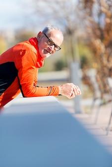 Frontowy widok jeden starszy biegacza mężczyzna z sportswear obsiadaniem na drewnianym ogrodzeniu podczas gdy patrzejący kamerę