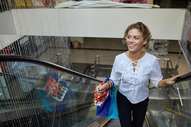 Frontowy widok jedzie up na eskalatorze w centrum handlowym żeński klient