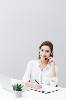 Frontowy widok jest ubranym słuchawki i pracuje przy biurkiem z laptopem kobieta