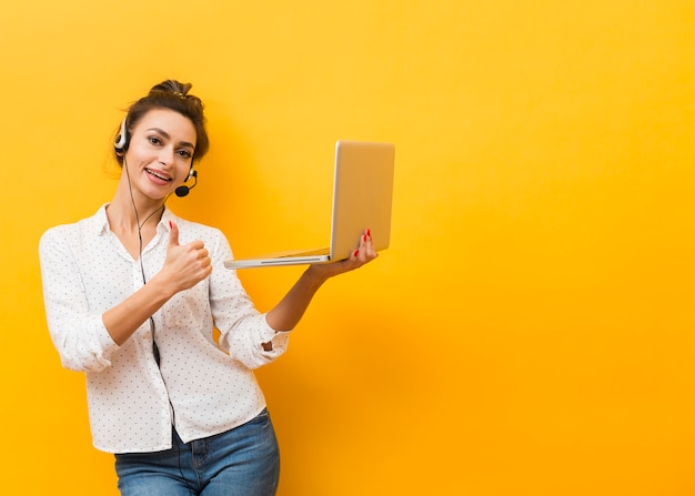 Frontowy widok jest ubranym słuchawki i trzyma laptop kobieta