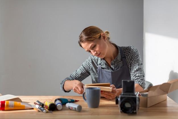 Frontowy widok kobieta przy biurka mienia książką
