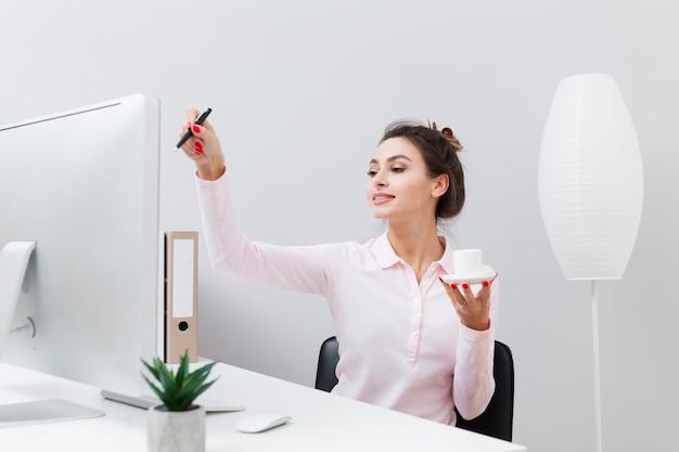 Frontowy widok kobieta trzyma filiżankę kawy przy biurkiem