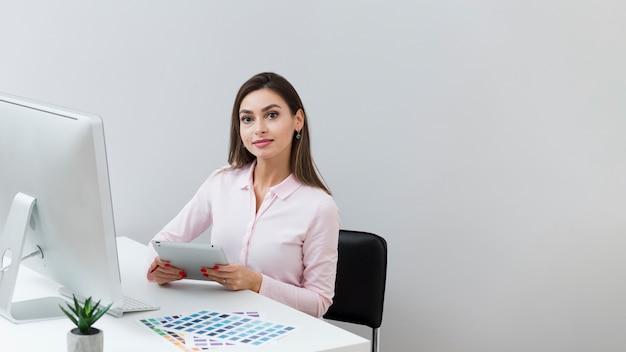 Frontowy widok kobieta trzyma pastylkę przy pracą