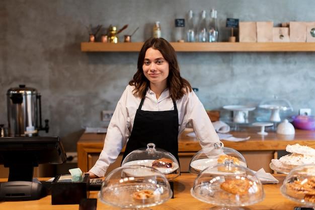 Frontowy widok kobieta w fartuchu przy sklep z kawą