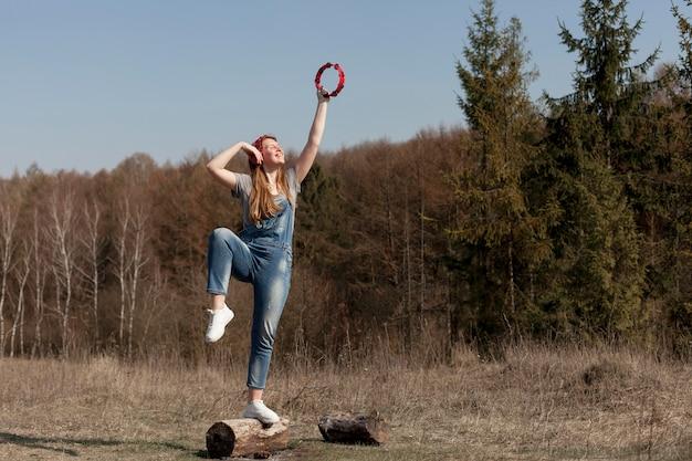 Frontowy widok kobieta w natury mienia tambourine