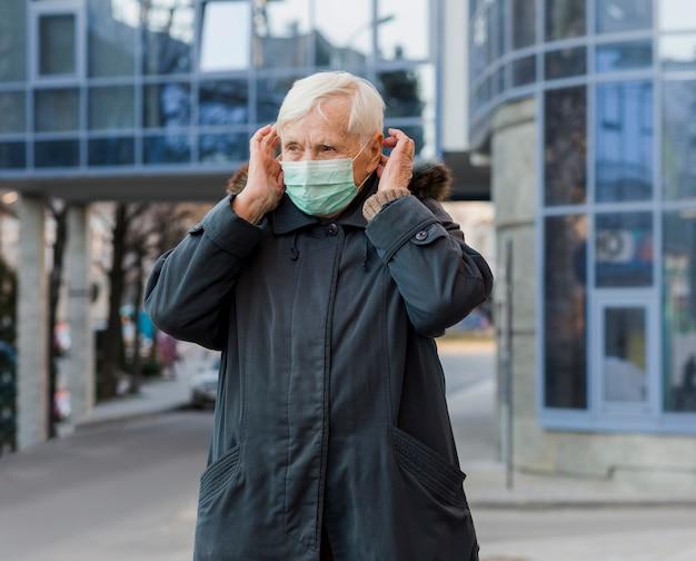 Frontowy widok kobieta z medyczną maską w mieście