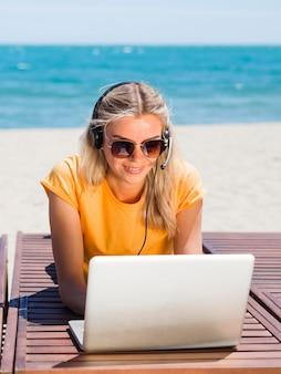 Frontowy widok kobieta z słuchawki i laptopem pracuje przy plażą