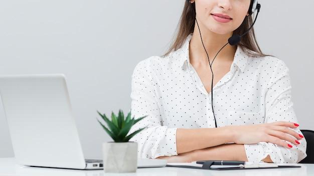 Frontowy widok kobieta z słuchawki pozuje przy biurkiem