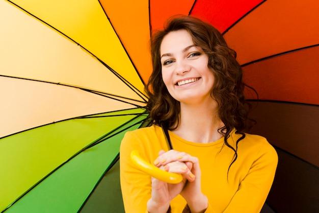 Frontowy widok kobieta z tęcza parasolem