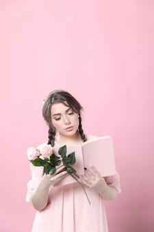 Frontowy widok kobiety czytelnicza książka podczas gdy trzymający róże