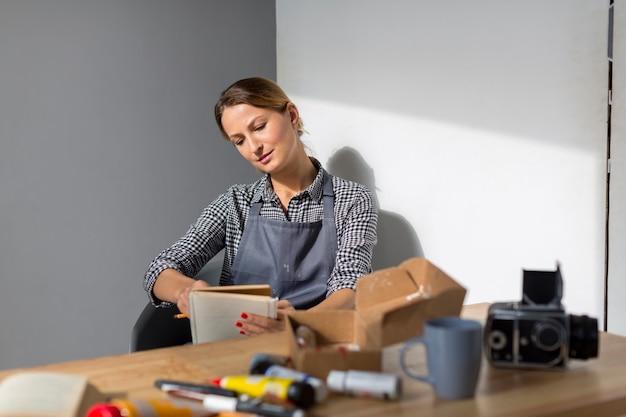 Frontowy widok kobiety mienia książka przy biurkiem