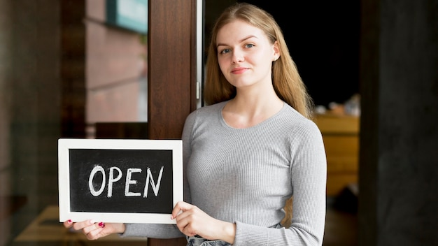 Frontowy widok kobiety mienia otwarty znak dla sklep z kawą