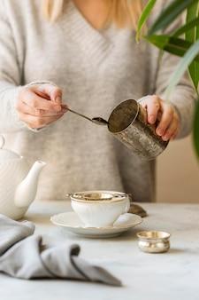 Frontowy widok kobiety narządzania herbata