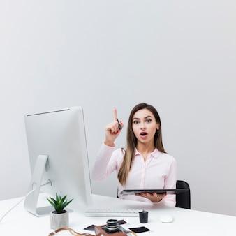 Frontowy widok kobiety obsiadanie przy biurkiem i mieć pomysł