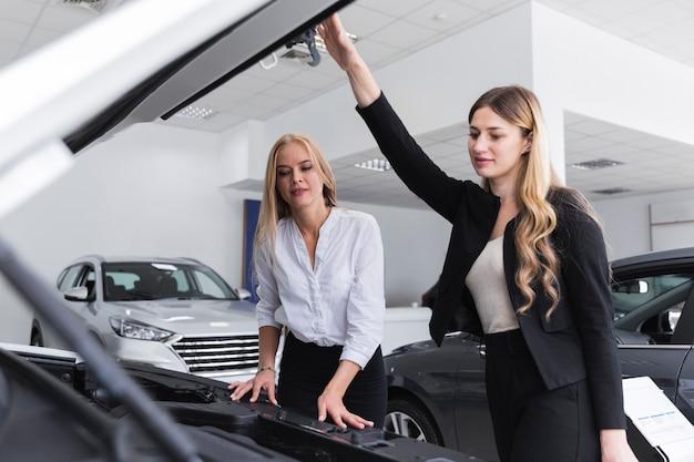 Frontowy widok kobiety sprawdza samochodowego silnika