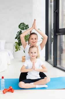 Frontowy widok matka i córka w joga pozujemy w domu