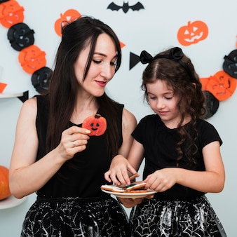 Frontowy widok matka i córka z talerzem ciastka