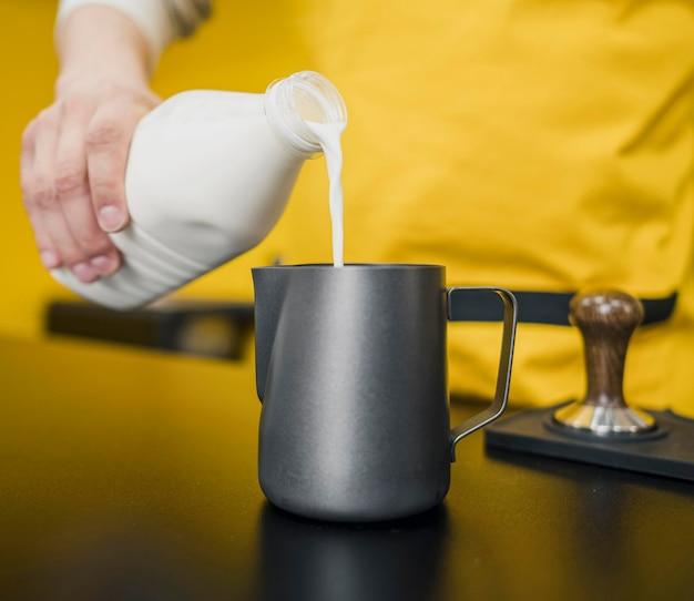 Frontowy widok męski barista dolewania mleko
