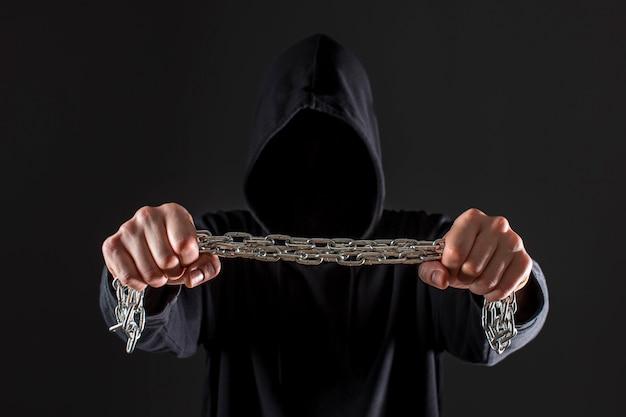 Frontowy widok męski hackera mienia metalu łańcuch w rękach