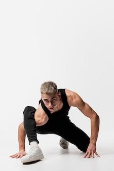 Frontowy widok męski tancerz w cajgach i podkoszulku bez rękawów pozuje z kopii przestrzenią