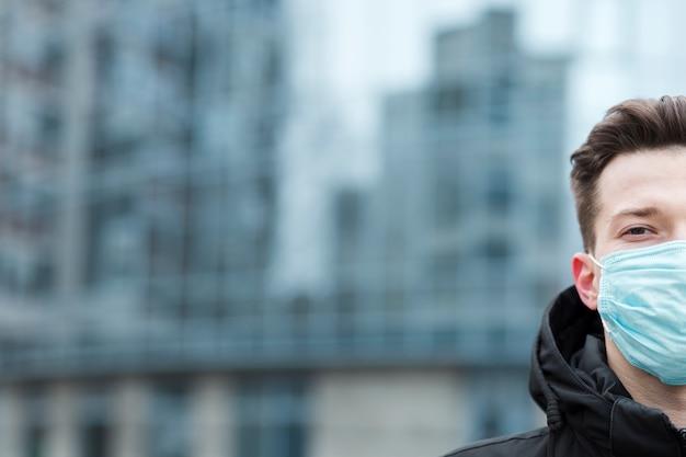 Frontowy widok mężczyzna jest ubranym medyczną maskę z kopii przestrzenią w mieście