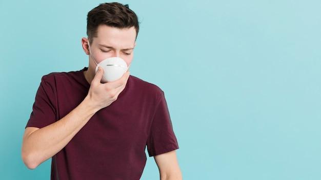 Frontowy widok mężczyzna jest ubranym medyczną maskę z koronawirusem