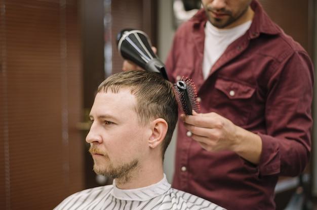 Frontowy widok mężczyzna ma jego włosy suszącego