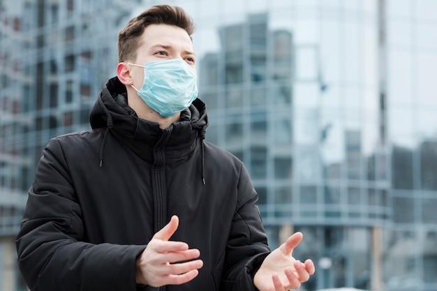 Frontowy widok mężczyzna z medyczną maską i defocused miastem