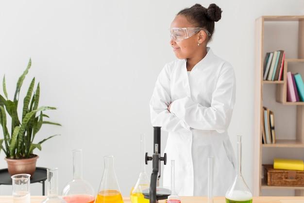 Frontowy widok młoda dziewczyna naukowiec w lab żakiecie z mikroskopu i kopii przestrzenią
