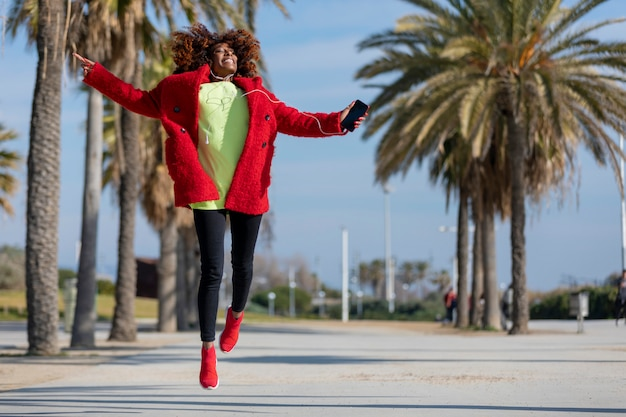 Frontowy widok młoda piękna kędzierzawa amerykanin afrykańskiego pochodzenia kobiety doskakiwanie, taniec i podczas gdy słuchający muzyczny i ono uśmiecha się outdoors