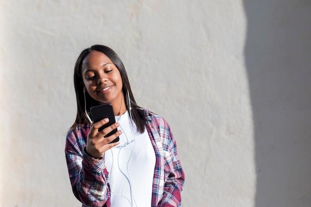 Frontowy widok młoda uśmiechnięta amerykanin afrykańskiego pochodzenia kobieta stoi outdoors podczas gdy ono uśmiecha się i słucha muzykę słuchawkami w słonecznym dniu