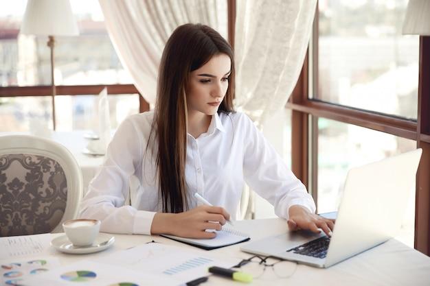 Frontowy widok młody brunetka bizneswoman który pracuje na laptopie i pisze coś puszkowi
