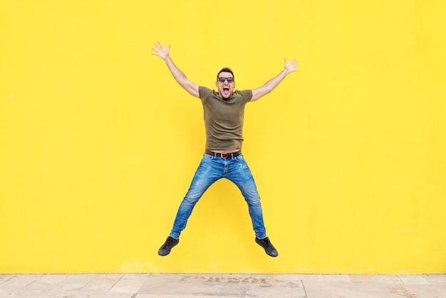Frontowy widok młody człowiek jest ubranym okulary przeciwsłonecznych skacze przeciw żółtej jaskrawej ścianie w słonecznym dniu