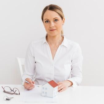 Frontowy widok młody fachowy agent nieruchomości jest usytuowanym w biurowej patrzeje kamerze