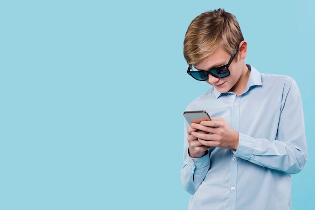 Frontowy widok nowożytny chłopiec mienia smarphone z kopii przestrzenią