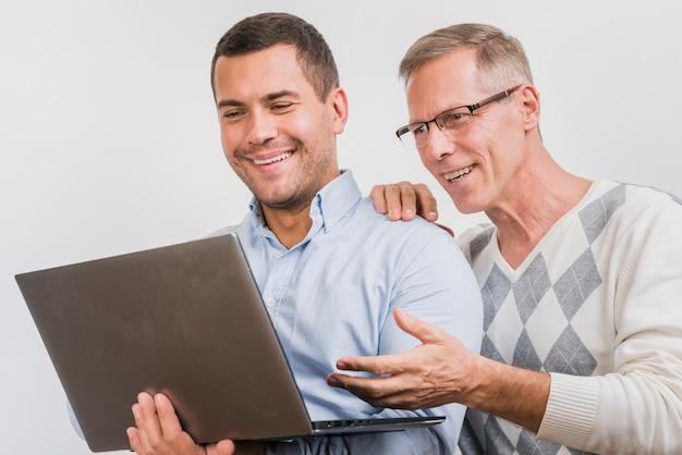 Frontowy widok ojciec i syn patrzeje laptop