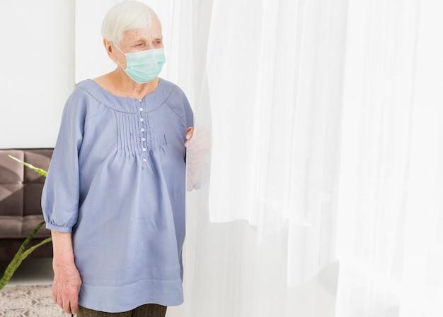 Frontowy widok patrzeje przez okno starsza kobieta podczas gdy będący ubranym medyczną maskę